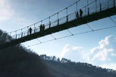 Reflection of people walking across a suspension bridge Stock Photography