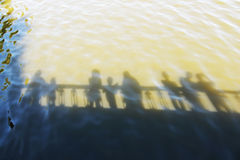 Reflection of people on the water. Silhouettes on the water of group of people standing on the bridge Stock Photography