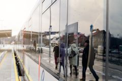 Reflection of people in the window of a passenger train car. People rush to the train. Reflection of people in the window of a passenger train car Royalty Free Stock Photo