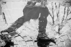 reflection of a person walking in a puddle in the rai