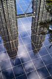 Reflection of PETRONAS Twin Towers. On with the palm leaves framing the picture Royalty Free Stock Photography