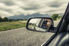 Reflection of a photographer with a camera in the rear view mirror of a car. Royalty Free Stock Photography