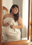 Reflection of Pregnant Latina Woman with Flower. Mirror reflection of happy expecting mother in white satin holding a pink carnation Royalty Free Stock Photos