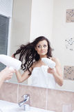 Reflection of pretty woman drying hair Stock Image