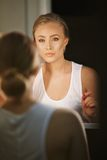 Reflection of pretty young woman in the mirror Stock Photography
