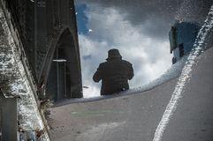 Reflection in a puddle of a man walking in the street Stock Images