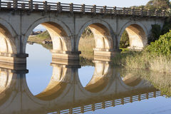 Reflection of a railway bridge crossing a lagoon on the KZN South Coast of South Africa. The single railway line running down the South Coast keeps close to the Stock Image