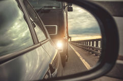Reflection in the rear-view mirror of the car, the cargo with the lights on. Royalty Free Stock Photo