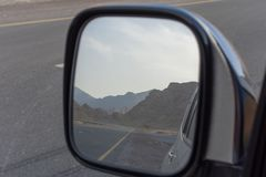 Reflection in rear view side mirror of road while driving along Jebal Jais Mountain road in Ras al Khaimah, United Arab Emirates stock image