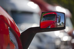 Reflection of the red truck in modern style mirror. Original reflection of the contemporary red semi truck in his own rear-view mirror, as well as displaying a Stock Photo