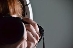 Reflection of a redhead girl in headphones and with a camera stock images