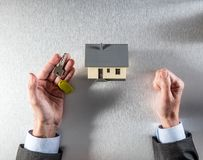 Reflection for renting, selling or buying house in businessman hands. Reflection for renting, selling or buying your house with the symbol of a home key in Royalty Free Stock Image