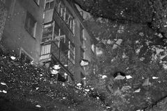 Reflection of a residential building in a puddle Stock Images