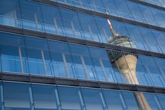 Reflection of the Rhine Tower. Telecommunications tower reflected in the glass facade of a modern skyscraper Royalty Free Stock Photography