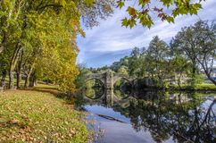 Medieval bridge over Arnoia river in Allariz, Ourense, Spain, in. Reflection of river and medieval bridge in Allariz in autumn , Orense, Galicia, Spain royalty free stock photography
