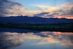 Sunset with sillhoutte mountains on background. Reflection on river from sunset Royalty Free Stock Image