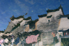 The reflection in a river of a  traditional fork house in Southern China Stock Photos