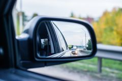 The reflection of the road with cars in the rearview mirror car traffic in the evening. Background backdrop Stock Photography