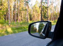 Reflection of road in the forest at the car side mirror. Stock Photos