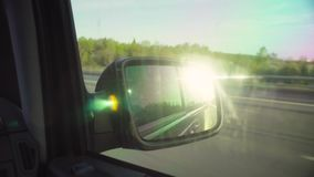 Reflection of the road in rearview mirror of a car. Reflection of the road, sky and sun in rearview mirror of the moving car stock video footage