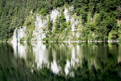 Reflection of rocks and forest in Alpine lake. Royalty Free Stock Images