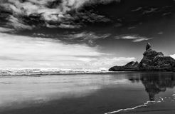 Piha beach. Reflection of rocks in the wet sand on the beautiful Piha beach near Auckland, New Zealand. Dramatic balck and white Stock Photography