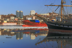 Reflection sailing ship and buildings of the city of Vladivostok in winter sea surface Royalty Free Stock Images