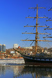 Reflection sailing ship and buildings of the city of Vladivostok in winter sea surface Stock Image