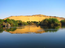 Reflection of a sand dune over the Nile river Stock Photography