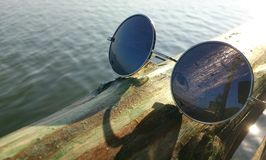 Reflection of sea in glasses. Sunglasses lying on wooden border near the water on seaside in sunny day Stock Image