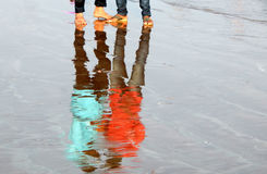 Reflection in sea tide of people in the beach Royalty Free Stock Images