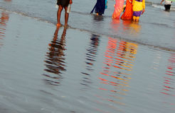 Reflection in sea tide of people in the beach Stock Photos