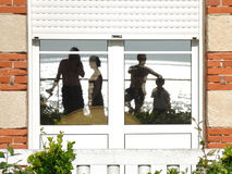 Reflection at the seaside. Family in front of the sea mirroring to the house's window Stock Photo