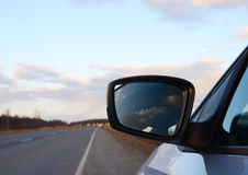 Reflection seen through car side mirror. Sunset Royalty Free Stock Photography