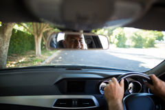 Reflection of senior man on mirror in car Stock Image