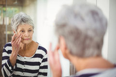 Reflection of senior woman looking at skin in mirror Royalty Free Stock Photography