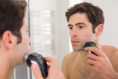 Reflection of shirtless man shaving with electric razor. Reflection of a handsome young shirtless man shaving with electric razor stock images