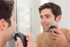 Reflection of shirtless man shaving with electric razor Royalty Free Stock Image