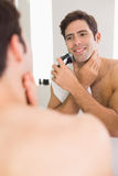 Reflection of shirtless man shaving with electric razor Stock Photo