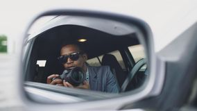 Reflection in side mirror of Paparazzi man sitting inside car and photographing with dslr camera Stock Photo