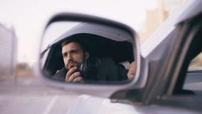 Reflection in side mirror of young private detective man sitting inside car and photographing with dslr camera Royalty Free Stock Photo