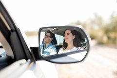 Reflection in side view mirror of couple traveling by car. Happy couple traveling by car. Reflection of beautiful young couple looking away and smiling while stock image