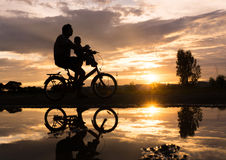Reflection Silhouette of Father with his toddler on bicycle agai Stock Images