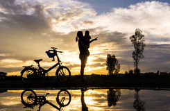 Reflection Silhouette of mother with her toddler against the sun Stock Photography