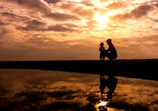 Reflection Silhouette of mother with her toddler against the sun Stock Image