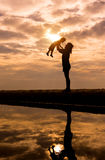 Reflection Silhouette of mother with her toddler against the sun Royalty Free Stock Photo