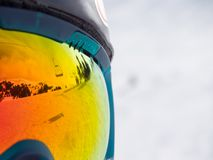 Reflection of a ski lifts in googles. Close up of colorfull googles that reflecting the landscape of a ski resort with lift Royalty Free Stock Photography