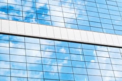Reflection of the sky and clouds in building windows close up Stock Photos