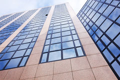Reflection of sky and clouds in modern office building Stock Photos