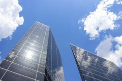 Reflection of sky and clouds on tall modern skyscrapers looking up with lens flare stock photography